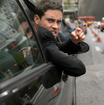 Angry Man Looking Out His Car Window Pointing