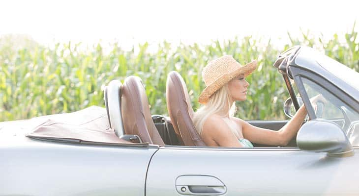 woman driving white convertible