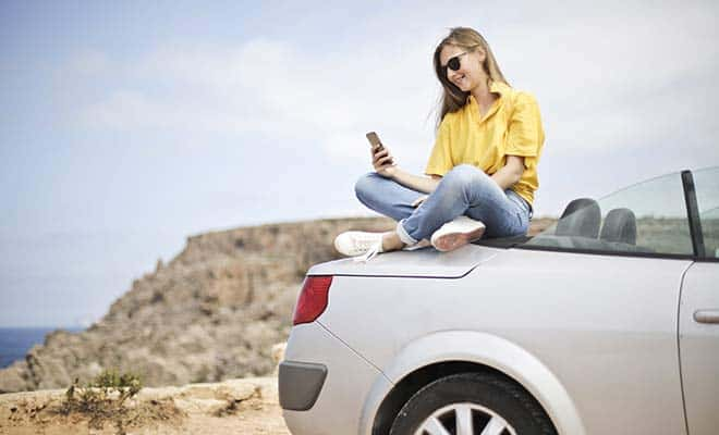 girl on phone by beach