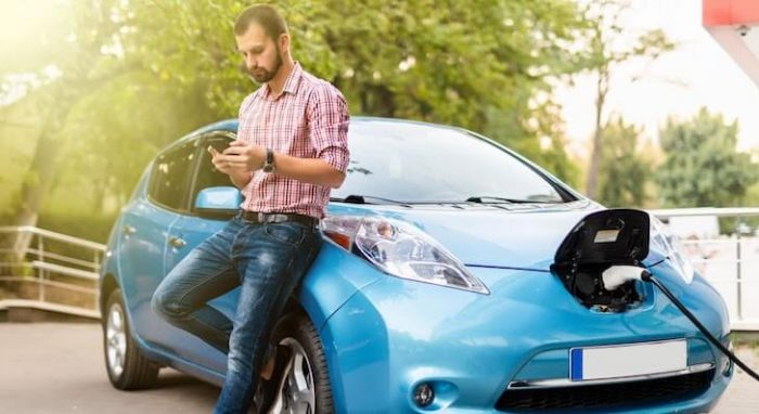 Man charges blue electric car