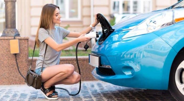 A woman charging her electric car