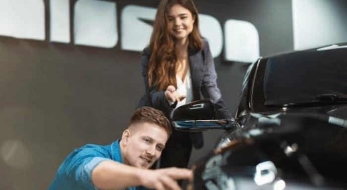 Couple examining a used electric car