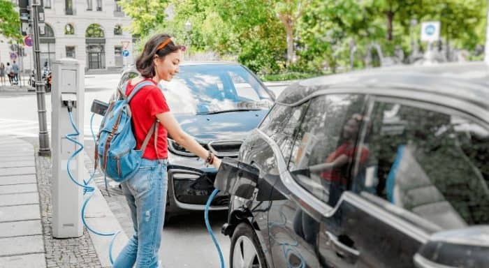 An electric car charging in the street