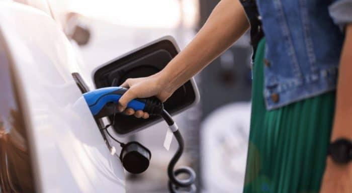 Woman plugs in electric car