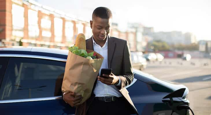 Man with groceries on phone next to electric car