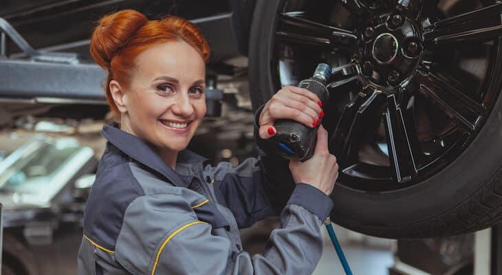 Electric car mechanic smiles at camera