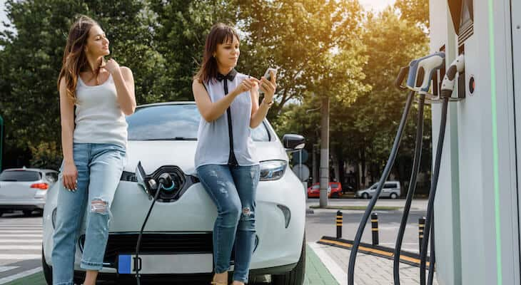 Two friends charge an electric car