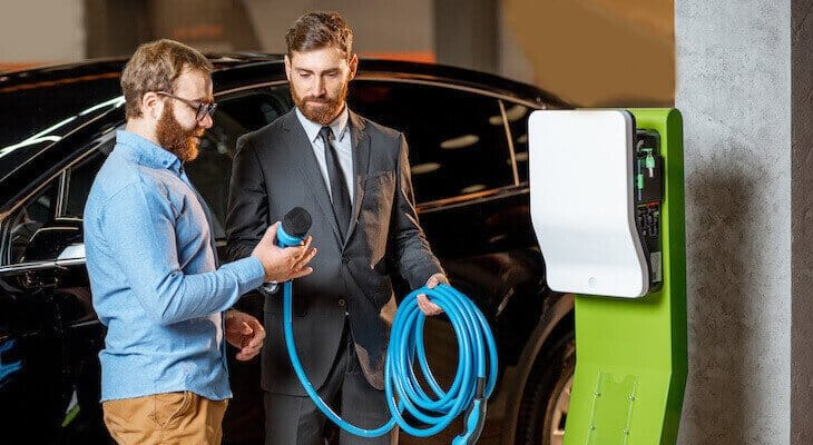 Two friends charging their electric vehicle