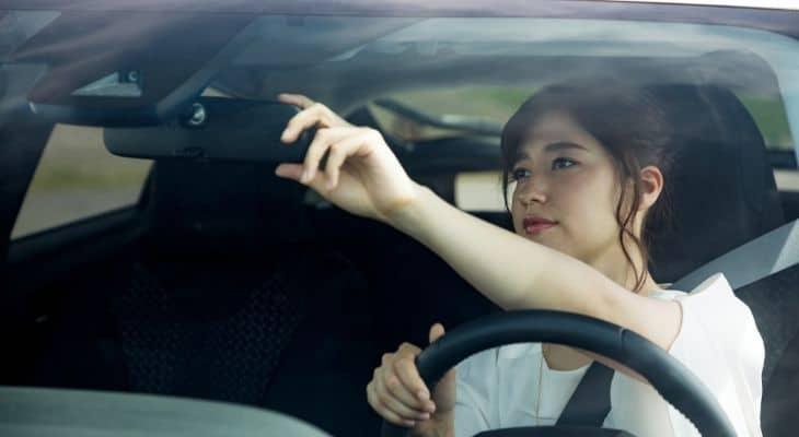 Woman adjusts her rearview mirror