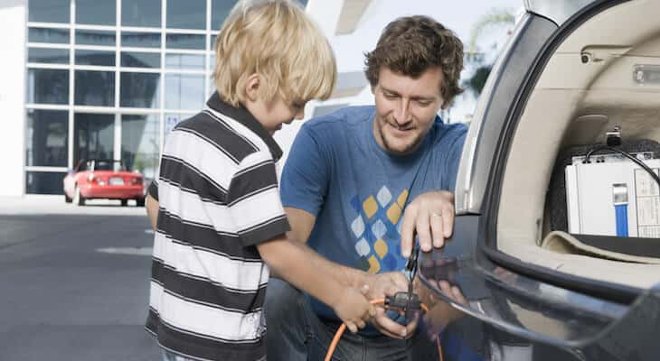 Father and son charge their electric vehicle
