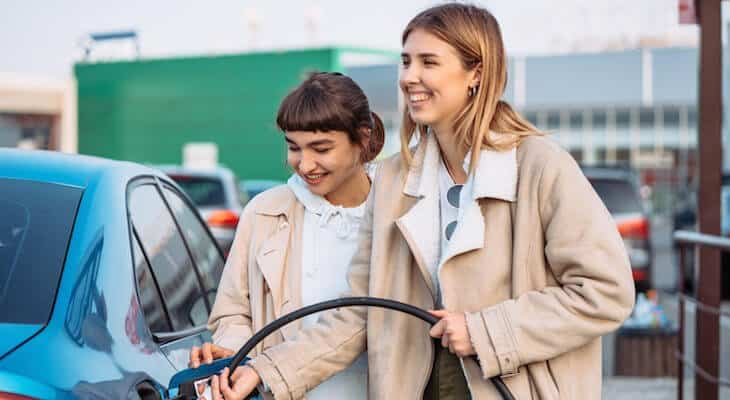Two friends charge an electric car together