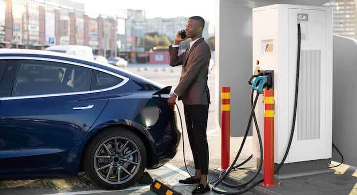 Man charges a blue Tesla