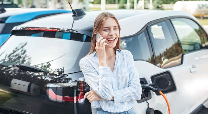 Woman talking on phone while charging electric car