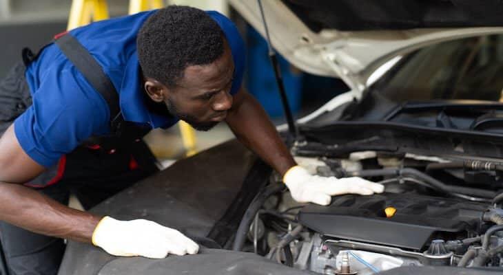 Mechanic performs maintenance on electric car