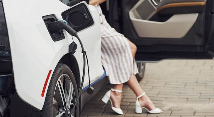 Woman sits while charging an electric car