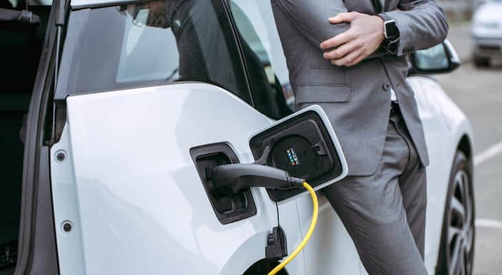 Businessman stands by a hybrid vehicle