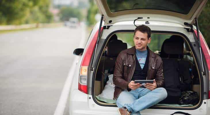 Man sits in trunk of white hybrid