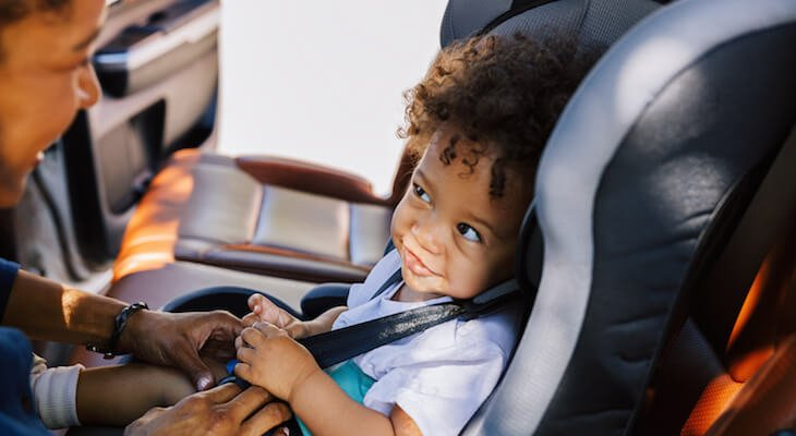 Baby in carseat smiles at parent