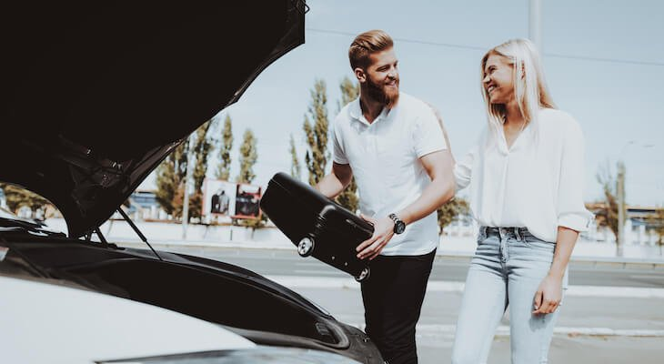 Tesla cost of ownership: Couple loads suitcase into Tesla