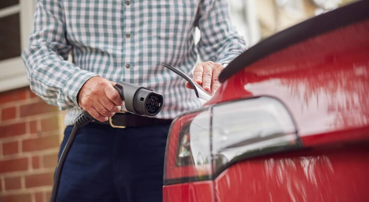 Advantages of electric cars: Man about to charge his car at home