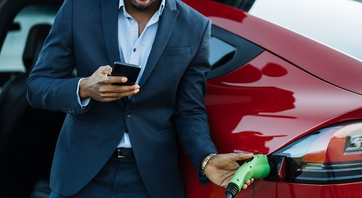 Upcoming electric cars: Man in a suit charging his electric car