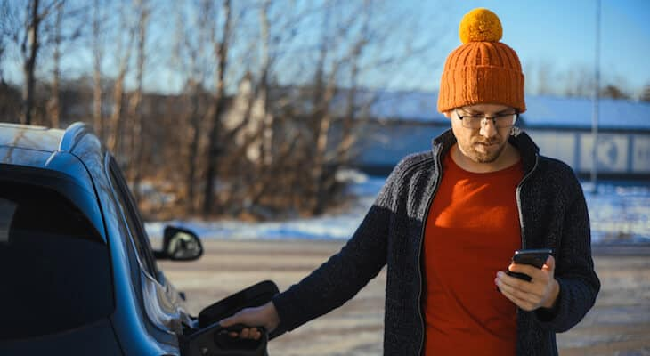 Man in beanie holds plug-in hybrid charging cable