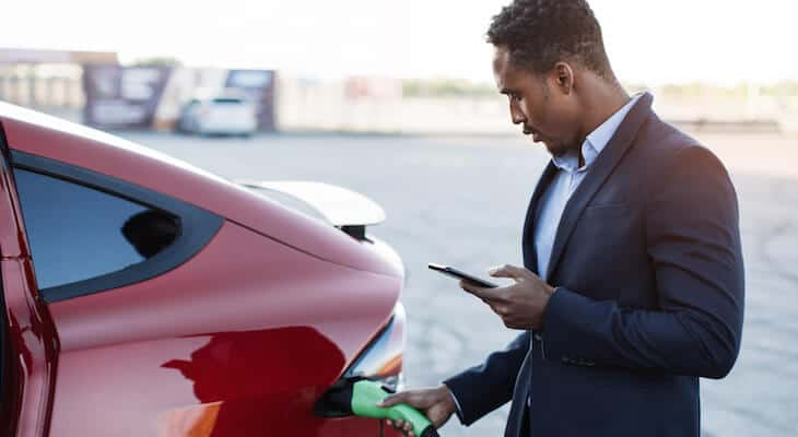 Man on phone charges red plug-in hybrid