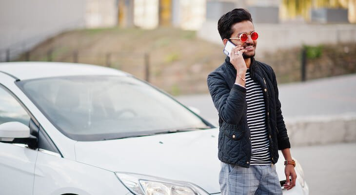 Advantages of electric cars: Man standing in front of a car on the phone