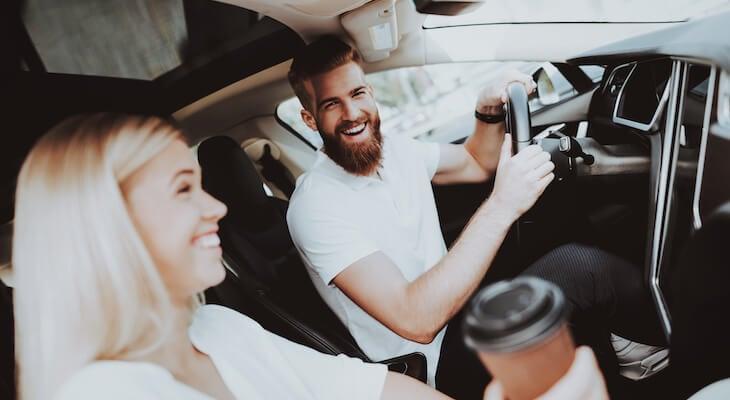 Tesla cost of ownership: Man smiles at woman in Tesla