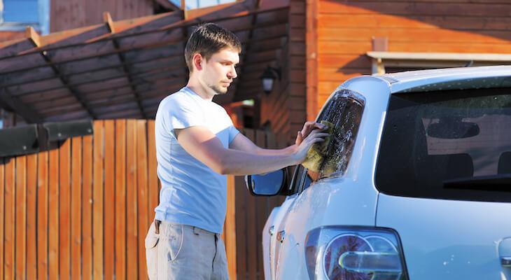 Man washes white car with sponge