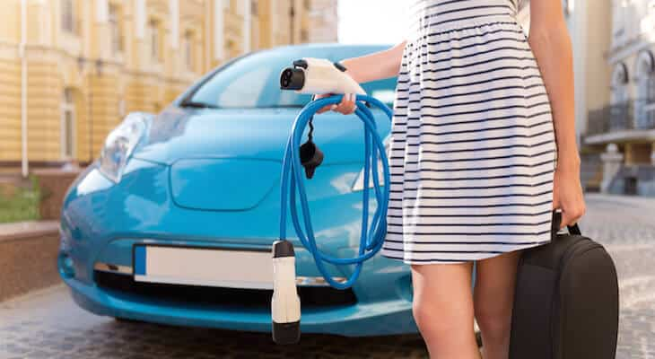 Woman holds plug-in hybrid charging cords