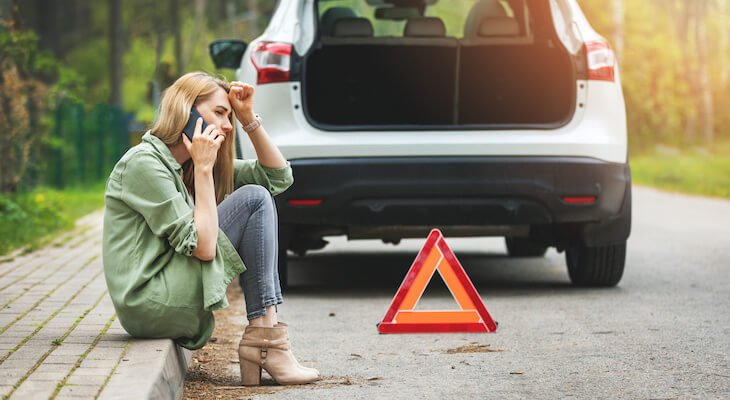 Woman sitting on road on the phone after car breaks down