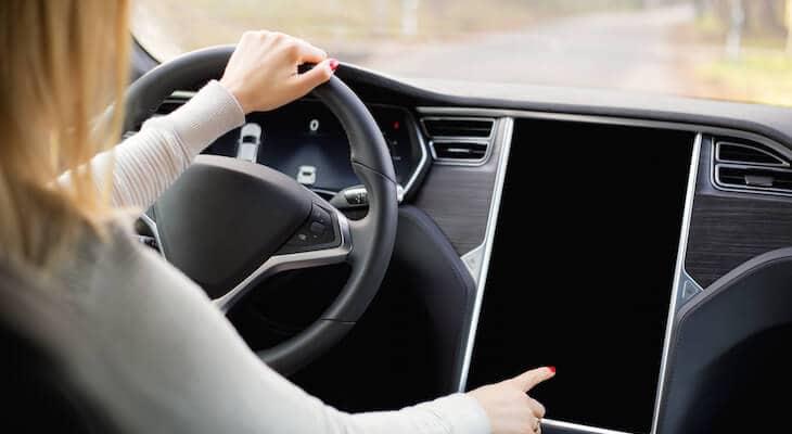 Woman using a Tesla touchscreen