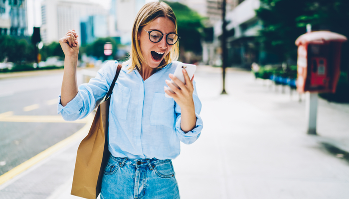 Woman looking at phone excited about her paperless discount