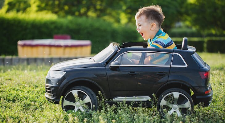 Small electric cars: little boy driving a toy car