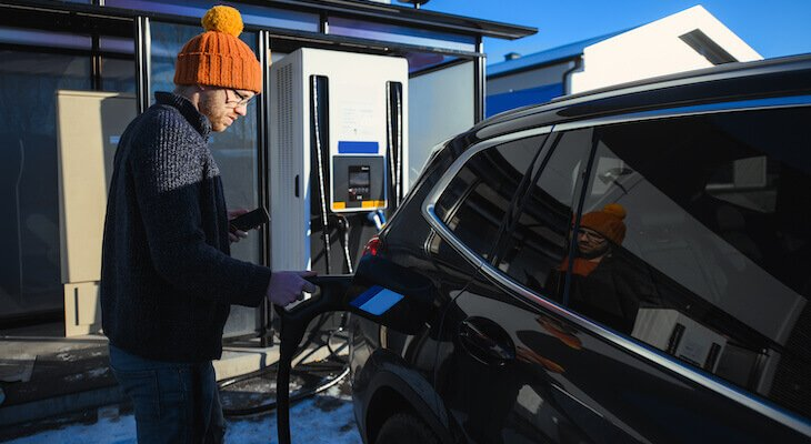 All wheel drive electric car: man charging his electric car