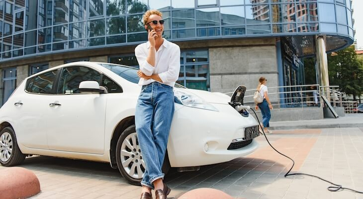 Top electric car companies: person talking on the phone while charging his electric car