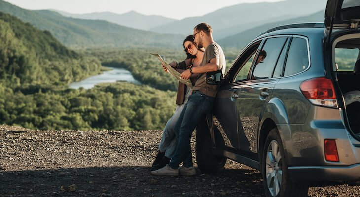Electric crossover: couple outside of their car looking at a map