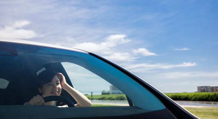 Most reliable hybrid cars: woman happily driving under the blue skies